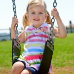 8726868-young-child-on-swing-in-playground-outdoors